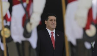 FILE - In this Aug. 21, 2017 file photo, then Paraguay's President Horacio Cartes stands for the playing of his country's national anthem during a welcome ceremony at the Planalto Presidential Palace, in Brasilia, Brazil. Brazilian police are seeking the arrest of Cartes as part of an investigation into kickbacks and money laundering. Federal prosecutors said Tuesday, Nov. 19, 2019, that Cartes is among 20 suspects being sought by Brazilian police. (AP Photo/Eraldo Peres, File)
