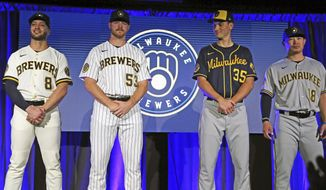 Milwaukee Brewers baseball players, from left,  Ryan Braun, Brandon Woodruff, Brent Suter and Keston Hiura show off the new team uniforms at Miller Park in Milwaukee, Monday, Nov. 18, 2019.  (Angela Peterson/Milwaukee Journal-Sentinel via AP)