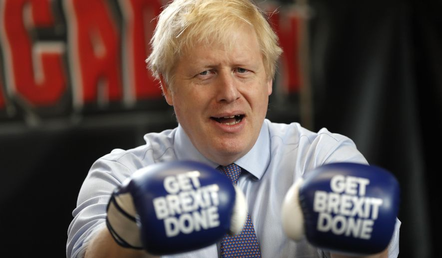 Britain's Prime Minister Boris Johnson poses for a photo wearing boxing gloves during a stop in his General Election Campaign trail at Jimmy Egan's Boxing Academy in Manchester, England, Tuesday, Nov. 19, 2019. Britain goes to the polls on Dec.12. (AP Photo/Frank Augstein)