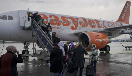 FILE - In this Thursday Oct. 18, 2012 file photo, passengers board a London-bound EasyJet flight at Amsterdam's Schiphol airport, Netherlands. European budget airline easyJet said Tuesday Nov. 19, 2019, that it will become the first major carrier to operate net-zero carbon flights, offsetting carbon emissions from the fuel used on every flight. (AP Photo/Peter Dejong, File)