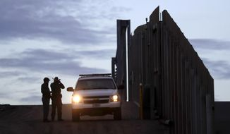 In this Wednesday, Nov. 21, 2018, photo, United States Border Patrol agents stand by a vehicle near one of the border walls separating Tijuana, Mexico, and San Diego, in San Diego. (AP Photo/Gregory Bull) ** FILE **