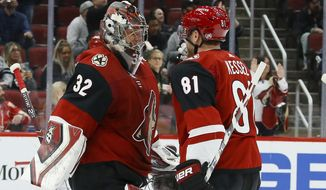 Arizona Coyotes goaltender Antti Raanta (32) smiles as he celebrates a shutout win against the Los Angeles Kings with Coyotes center Phil Kessel (81) as time expires in the third period of an NHL hockey game, Monday, Nov. 18, 2019, in Glendale, Ariz. The Coyotes defeated the Kings 3-0. (AP Photo/Ross D. Franklin)