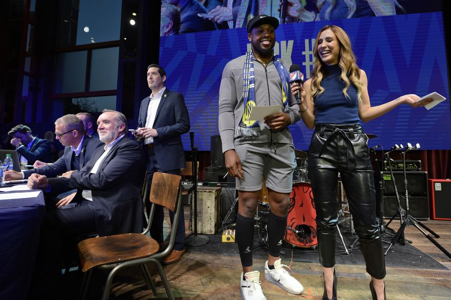 Tennessee Titans running back Derrick Henry laughs with MLS host Susannah Collins before announcing the team's second selection during the Major League Soccer expansion draft Tuesday, Nov. 19, 2019, in Nashville, Tenn. Nashville SC selected Zarek Valentin from the Portland Timbers. (AP Photo/Mark Zaleski)