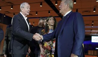 While first lady Tammy Murphy, center, looks on, former Vice President Al Gore, right, shake hands with New Jersey Governor Phil Murphy after a signing ceremony at Liberty Science Center in Jersey City, N.J., Tuesday, Nov. 19, 2019. Murphy signed an executive order that commits the state to produce 7,500 megawatts of electricity through wind energy by 2035. That's more than double the goal Murphy previously set of 3,500 megawatts by 2030. (AP Photo/Seth Wenig)