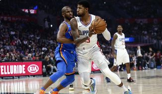 Los Angeles Clippers' Paul George (13) drives against Oklahoma City Thunder's Chris Paul (3) during the first half of an NBA basketball game, Monday, Nov. 18, 2019, in Los Angeles. (AP Photo/Ringo H.W. Chiu)