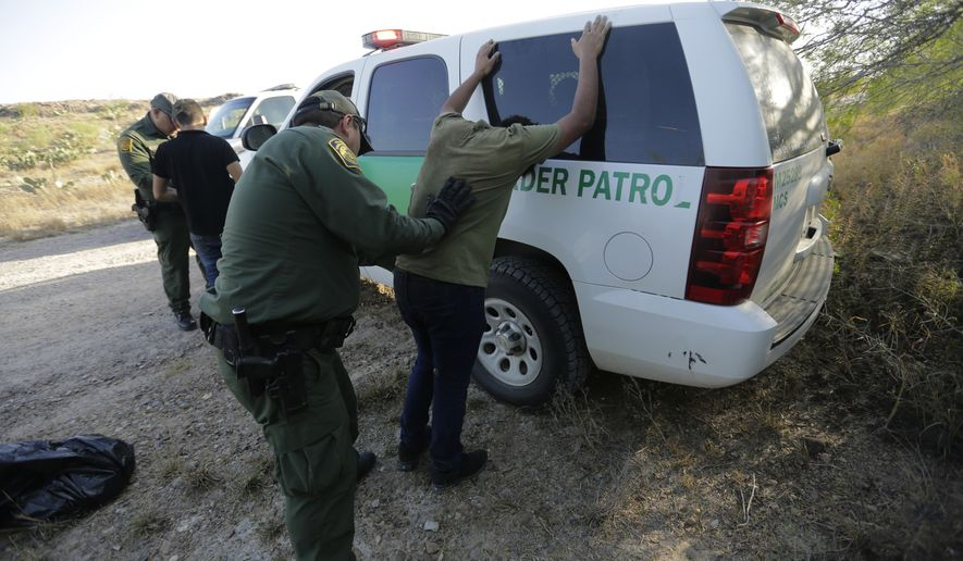 In this Wednesday, Nov. 6, 2019, photo, Border Patrol agents stop two men thought to have entered the country illegally, near McAllen, Texas, along the U.S.-Mexico border. In the Rio Grande Valley, the southernmost point of Texas and historically the busiest section for border crossings, the U.S. Border Patrol is apprehending around 300 people daily, down from as many as 2,000 people a day in May. (AP Photo/Eric Gay)