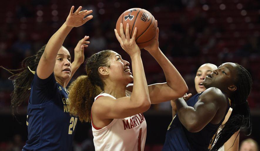 Maryland's Shakira Austin, center, shoots as George Washington's Sarah Overcash, left, and Mayowa Taiwo defend during an NCAA basketball game on Wednesday, Nov. 20, 2019 in College Park, Md. (AP Photo/Gail Burton)