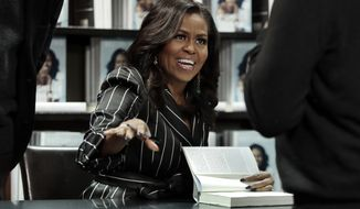 """FILE - This Nov. 30, 2018 file photo shows former first lady Michelle Obama signing books during an appearance for her book, """"Becoming,"""" in New York. Obama earned a Grammy nomination for best spoken word album for her book. Barack Obama won best spoken word album twice _ in 2006 for Dreams from My Father and in 2008 for The Audacity of Hope. (AP Photo/Richard Drew, File)"""