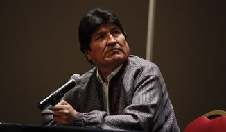 Former Bolivian President Evo Morales, who was granted asylum in Mexico, looks up toward a video playing on a screen during a press conference in Mexico City, Wednesday, Nov. 20, 2019. (AP Photo/Rebecca Blackwell)