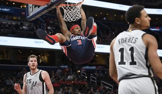 Washington Wizards guard Bradley Beal (3) hangs from the rim after his dunk between San Antonio Spurs center Jakob Poeltl (25) and guard Bryn Forbes (11) during the first half of an NBA basketball game Wednesday, Nov. 20, 2019, in Washington. (AP Photo/Nick Wass)