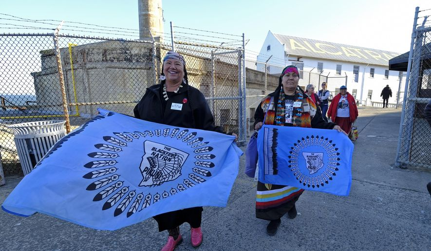 Theda New Breast, left, and Aurora Mamea, of the Blackfeet Nation in Montana, make their way to ceremonies for the 50th anniversary of the Native American occupation of Alcatraz Island Wednesday, Nov. 20, 2019, in San Francisco. About 150 people gathered at Alcatraz to mark the 50th anniversary of a takeover of the island by Native American activists. Original occupiers, friends, family and others assembled Wednesday morning for a program that included prayer, songs and speakers. They then headed to the dock to begin restoring messages painted by occupiers on a former barracks building. (AP Photo/Eric Risberg) **FILE**