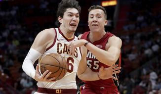 Cleveland Cavaliers forward Cedi Osman, left, drives to the basket as Miami Heat forward Duncan Robinson, right, defends during the first half of an NBA basketball game, Wednesday, Nov. 20, 2019, in Miami. (AP Photo/Lynne Sladky)