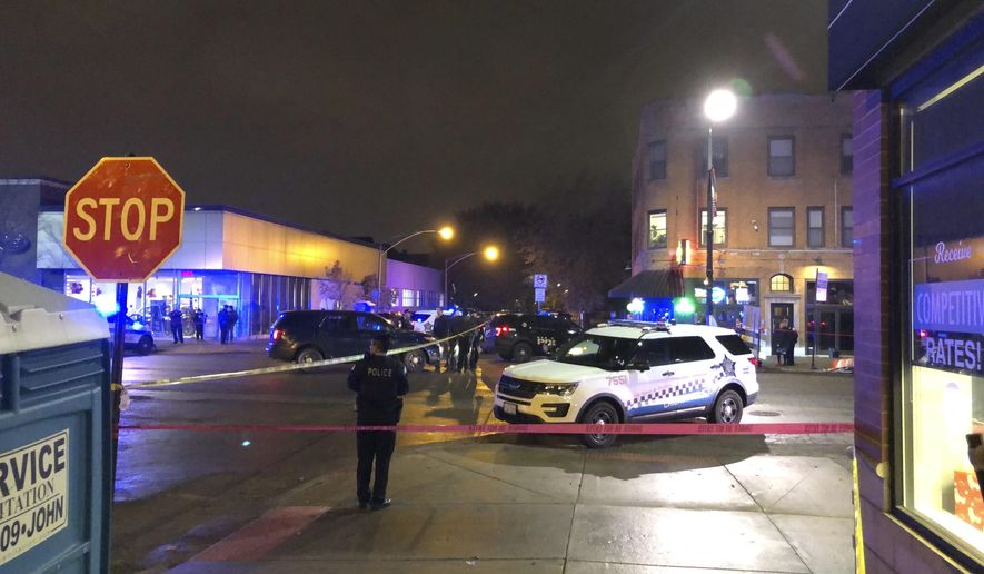 Chicago Police investigate the scene where an officer was shot by a suspected bank robber in the 4300 block of West Irving Park Road, Tuesday night, Nov. 19, 2019. A 15-year-old boy was also wounded in the shooting, while the suspect was shot and killed. (Sam Charles/Chicago Sun-Times via AP)