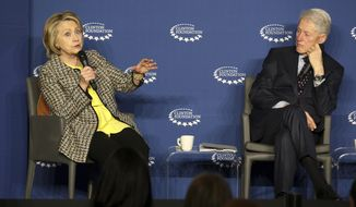 """Former Secretary of State Hillary Clinton speaks as her husband, former President Bill Clinton listens during a panel discussion at the """"Economic Inclusion and Growth: The Way Forward"""" conference on Wednesday, Nov. 20, 2019, at the Clinton Presidential Center in Little Rock, Ark. (Tommy Metthe/The Arkansas Democrat-Gazette via AP)"""