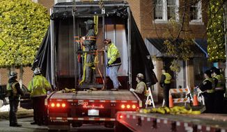 Workers load a Confederate statue onto a truck after it was removed from its spot in front of the historic Chatham County courthouse in Pittsboro, N.C. early Wednesday, Nov. 20, 2019. (Scott Sharpe/The News & Observer via AP)