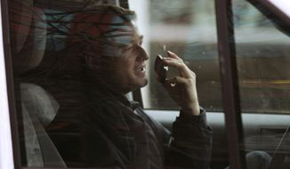 FILE - In this Dec. 14, 2011, file photo, a driver talks on a cell phone while driving through the Financial District of Boston. (AP Photo/Charles Krupa, File) **FILE**