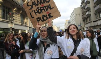 """Medical staffs hold a poster reading """"Save Public Hospitals"""" during a national demonstration Thursday, Nov. 14, 2019 in Paris. Thousands of exasperated nurses, doctors and other public hospital workers are marching through Paris to demand more staff and resources after years of cost cuts. (AP Photo/Michel Euler)"""