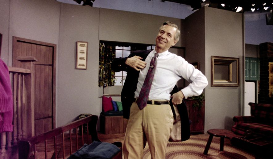 """Fred Rogers puts on his jacket between takes on the set of his television program """"Mister Rogers' Neighborhood"""" in Pittsburgh on June 8, 1993. (AP Photo/Gene J. Puskar)"""