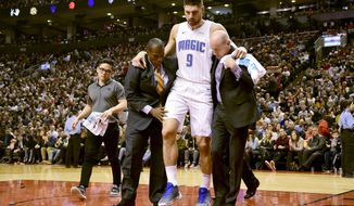 Orlando Magic center Nikola Vucevic (9) is taken off the court after an awkward landing during the first half of the team's NBA basketball game against the Toronto Raptors on Wednesday, Nov. 20, 2019, in Toronto. (Frank Gunn/The Canadian Press via AP)