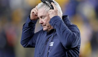 North Carolina coach Mack Brown adjusts his headset as he walks the sideline during the second half of the team's NCAA college football game against Pittsburgh, Thursday, Nov. 14, 2019, in Pittsburgh. Pittsburgh won 34-27 in overtime. (AP Photo/Keith Srakocic)