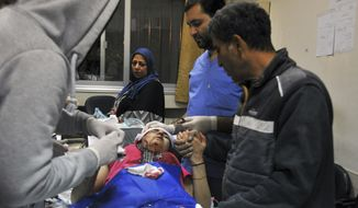 "In this photo released by the Syrian official news agency SANA, a paramedic treats an injured woman wounded by Israeli missile strikes at a hospital in Damascus, Syria, Wednesday, Nov. 20, 2019. The Israeli military on Wednesday said it struck dozens of Iranian targets in Syria, carrying out a ""wide-scale"" strike in response to rocket fire on the Israeli-controlled Golan Heights the day before. (SANA via AP)"
