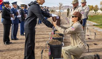 Seaman Alex Ramirez presents an urn for burial to Brandon Hall with the Southern Nevada Veterans Memorial Cemetery during the third Missing in Nevada ceremony on Tuesday, Nov. 19, 2019, in Boulder City. (L.E. Baskow/Las Vegas Review-Journal via AP)