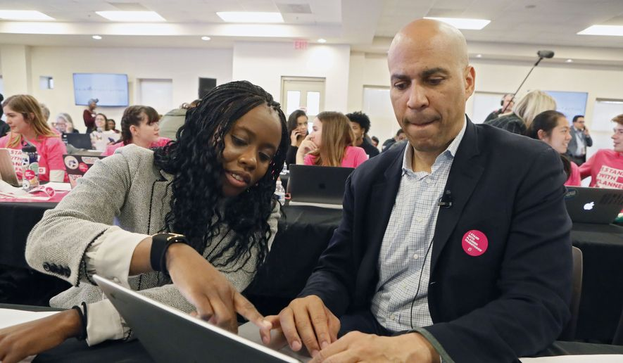 Democratic presidential candidate Sen. Cory Booker, D-J., right, gets some assistance from Esosa Osa while texting people on a call list as he participates in at a Fair Fight phone bank at Ebenezer Baptist Church, Thursday, Nov. 21, 2019, in Atlanta. Democratic presidential candidates including Cory Booker, Amy Klobuchar, Andrew Yang and Pete Buttigieg, along with Stacey Abrams, joined in at the phone bank in response to Georgia election officials' plan to cancel more than 313,000 voter registrations next month. (Bob Andres/Atlanta Journal-Constitution via AP)