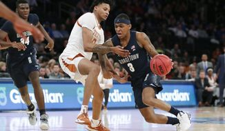 Texas forward Gerald Liddell (0) defends Georgetown guard James Akinjo (3) who drives to the basket during the second half of the first round of the 2K Empire Classic NCAA college basketball tournament, Thursday, Nov. 21, 2019, in New York. Georgetown defeated Texas 82-66. (AP Photo/Kathy Willens) ** FILE **