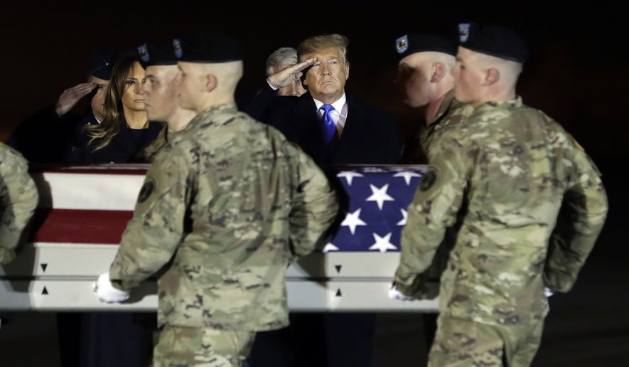 President Donald Trump and first lady Melania Trump watch as a U.S. Army carry team moves a transfer case containing the remains of Chief Warrant Officer 2 David C. Knadle, of Tarrant, Texas, Thursday, Nov. 21, 2019, at Dover Air Force Base, Del. According to the Department of Defense, Knadle died in Afghanistan when his helicopter crashed while providing security for troops on the ground in eastern Logar Province. (AP Photo/ Evan Vucci)