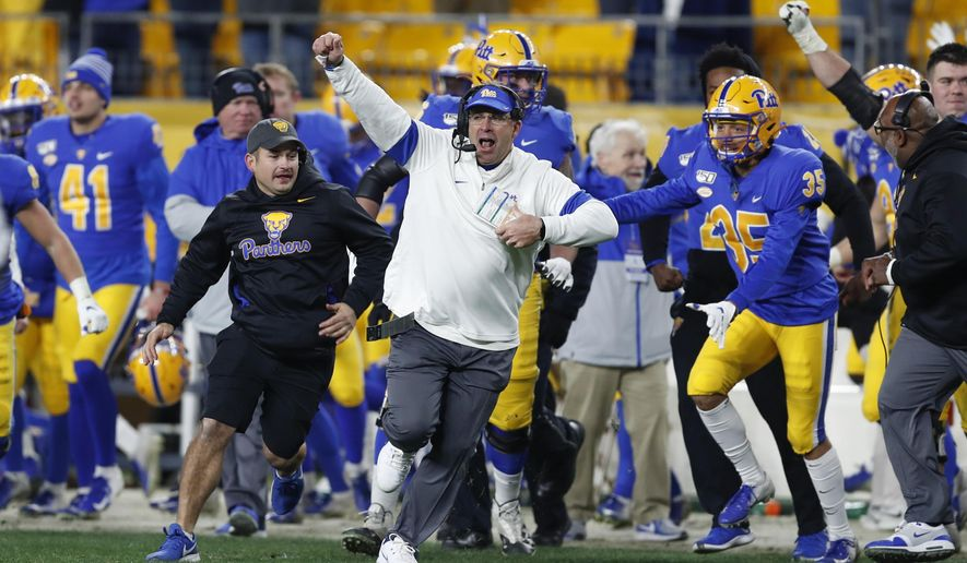 Pittsburgh coach Pat Narduzzi, center, celebrates with his team as they run onto the field after a fourth-down pass by North Carolina quarterback Sam Howell fell incomplete in the end zone during overtime of an NCAA football game Thursday, Nov. 14, 2019, in Pittsburgh. Pittsburgh won 34-27. (AP Photo/Keith Srakocic)