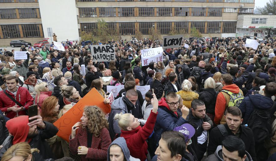 People attend a protest in Sarajevo, Bosnia, Thursday, Nov. 21, 2019. Protesters in Bosnia have rallied outside the government building in Sarajevo after opposition lawmaker Sabina Cudic published shocking photos of special needs children tied to beds and radiators in a nearby government facility. The protest Thursday by 1,000 people included scores of parents of children with disabilities, who described a dysfunctional care system that condemns their kids to suffering and excludes them from society. (AP Photo/Almir Alic)