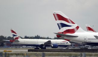 """FILE - In this Monday, Sept. 9, 2019 file photo, a British Airways plane, at left, is towed past other planes sitting parked at Heathrow Airport in London. British Airways says flights are being disrupted by a """"technical issue."""" Information from Heathrow, Britain's busiest airport, shows some trans-Atlantic flights delayed Thursday Nov. 21, 2019 by several hours. (AP Photo/Matt Dunham, File)"""