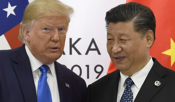 In this June 29, 2019, photo, U.S. President Donald Trump poses for a photo with Chinese President Xi Jinping during a meeting on the sidelines of the G-20 summit in Osaka, western Japan. (AP Photo/Susan Walsh) **FILE**