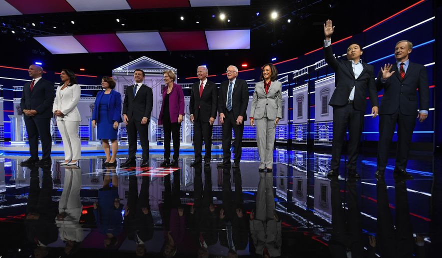 Democratic presidential candidates from left, Sen. Cory Booker, D-N.J., Rep. Tulsi Gabbard, D-Hawaii, Sen. Amy Klobuchar, D-Minn., South Bend, Ind., Mayor Pete Buttigieg, Sen. Elizabeth Warren, D-Mass., former Vice President Joe Biden, Sen. Bernie Sanders, I-Vt., Sen. Kamala Harris, D-Calif., former technology executive Andrew Yang and investor Tom Steyer wave to the audience before a Democratic presidential primary debate, Wednesday, Nov. 20, 2019, in Atlanta. (AP Photo/John Amis) ** FILE **
