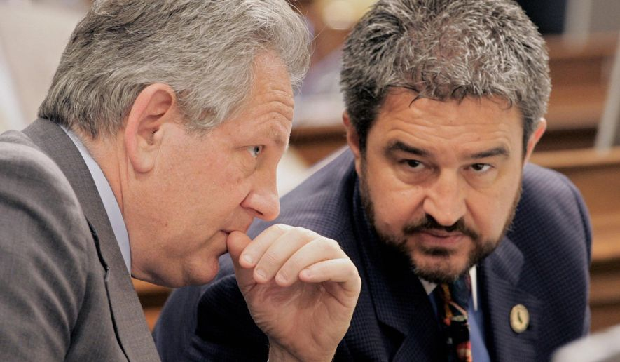 FILE - In this May 26, 2005 file photo Assembly members Keith Richman, R-Chatsworth, left, and Joe Canciamilla, D-Pittsburg, confer during a debate at the Capitol in Sacramento, Calif. Canciamilla, has been ordered to pay $150,000 in fines after an audit by the state's campaign ethics watchdog found he spent political contributions on a vacation in Asia, personal plane tickets and remodeling his vacation home in Hawaii. The Mercury News of San Jose reports that the Fair Political Practices Commission found Canciamilla violated campaign finance laws more than 30 times and used $130,529 in campaign funds from 2011 to 2015, and falsified state filings to cover it up. (AP Photo/Rich Pedroncelli,File)