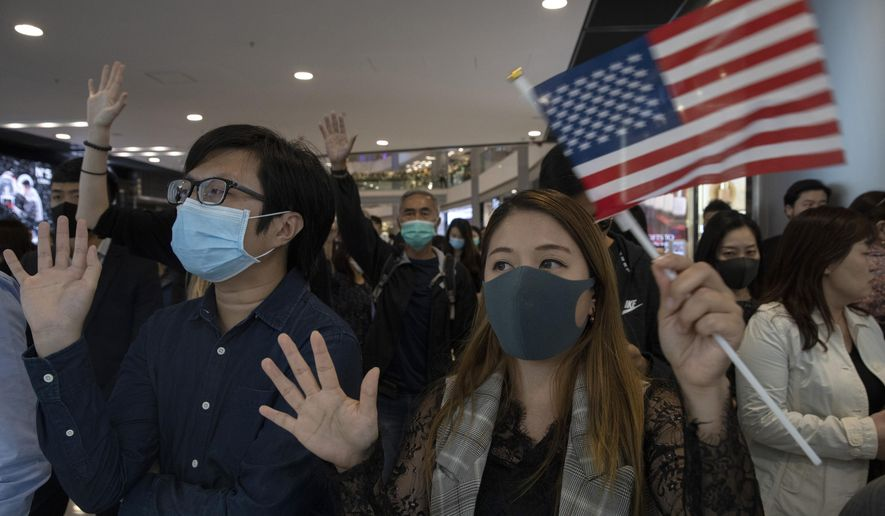 "Hongkongers hold up their hands to represent their five demands and a United States flag as they chant ""Pass the bill, save Hong Kong"" at the IFC mall in Hong Kong Thursday, Nov. 21, 2019. Pressure ratcheted up on Hong Kong as the U.S. Congress approved legislation late Wednesday to sanction officials who carry out human rights abuses and require an annual review of the favorable trade status that Washington grants Hong Kong. Another bill bans export of tear gas and other non-lethal tools to Hong Kong, (AP Photo/Ng Han Guan)"