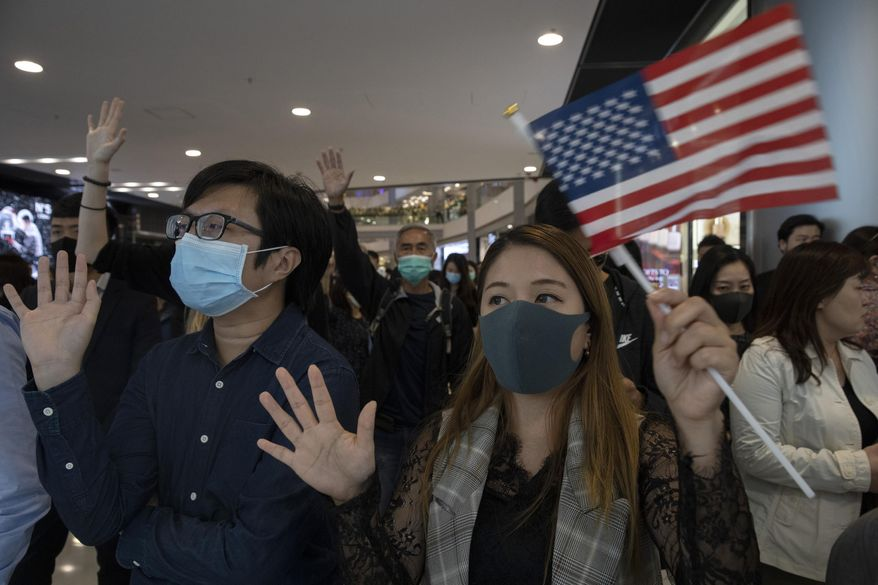 """Hongkongers hold up their hands to represent their five demands and a United States flag as they chant """"Pass the bill, save Hong Kong"""" at the IFC mall in Hong Kong Thursday, Nov. 21, 2019. Pressure ratcheted up on Hong Kong as the U.S. Congress approved legislation late Wednesday to sanction officials who carry out human rights abuses and require an annual review of the favorable trade status that Washington grants Hong Kong. Another bill bans export of tear gas and other non-lethal tools to Hong Kong, (AP Photo/Ng Han Guan)"""