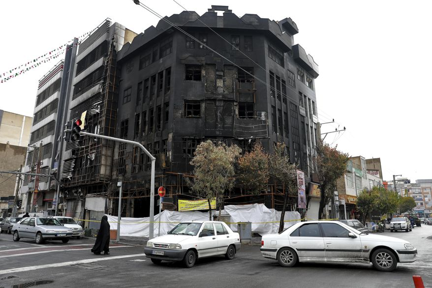 Traffic passes a building that was set ablaze during recent protests over government-set gasoline prices rises, in Tehran, Iran, Wednesday, Nov. 20, 2019. The demonstrations struck at least 100 cities and towns, spiraling into violence that saw banks, stores and police stations attacked and burned. (AP Photo/Ebrahim Noroozi)