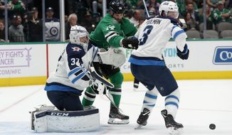Winnipeg Jets goaltender Connor Hellebuyck (37) and defenseman Tucker Poolman (3) defend against pressure from Dallas Stars left wing Jamie Benn (14) on an attack in the first period of an NHL hockey game in Dallas, Thursday, Nov. 21, 2019. (AP Photo/Tony Gutierrez)