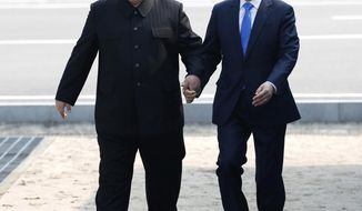 In this April 27, 2018, file photo, North Korean leader Kim Jong Un, left, and South Korean President Moon Jae-in cross the military demarcation line to the South side at the border village of Panmunjom in the Demilitarized Zone. North Korea on Thursday, Nov. 21, 2019, said Kim turned down an invitation by Moon to participate in a regional summit next week in the southern city of Busan and has blamed the South for a deep freeze in inter-Korean relations. (Korea Summit Press Pool via AP, File)