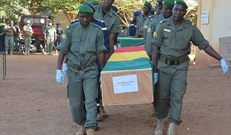 In this photo made available on the Mali Army twitter feed, showing coffins being honoured at a funeral ceremony in Gao, Mali, Wednesday Nov. 20, 2019.  The Mali Defense Ministry held a funeral for the 30 soldiers killed in a Monday attack on an army patrol by extremists near the border with Niger. (Mali Army via AP)