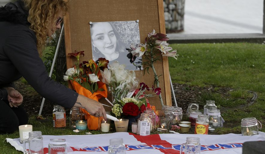 FILE - In this Dec. 12, 2018, file photo, a woman lights candles during a candlelight vigil for murdered British tourist Grace Millane at Cathedral Square in Christchurch, New Zealand. A New Zealand jury on Friday, Nov. 22, 2019,  was deliberating whether a British backpacker was murdered by a man she met on a dating app or was accidentally choked to death during sex. (AP Photo/Mark Baker, File)