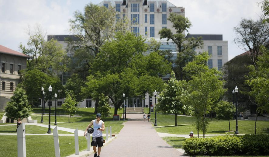 Pedestrians walk towards The Ohio State University's athletics facilities in Columbus, Ohio.  (AP Photo/John Minchillo, File)
