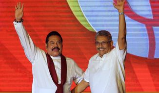 FILE - In this Aug. 11, 2019, file photo, former Sri Lankan President Mahinda Rajapaksa, left, and former Defense Secretary and his brother Gotabaya Rajapaksa wave to supporters during a party convention held to announce the presidential candidacy in Colombo, Sri Lanka. President Gotabaya Rajapaksa has sworn in his brother and former president Mahinda Rajapaksa as prime minister on Thursday, Nov. 21, in his first step in forming a government since being elected president. (AP Photo/Eranga Jayawardena, File)