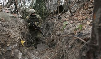 In this photo taken on Monday, Nov. 18, 2019, a Ukrainian soldier in a trench in the front line near the town of Avdiivka in the Donetsk region, Ukraine. U.S.-made X-ray equipment, helmets and missiles make a difference for Ukrainian troops fighting Kremlin-backed separatists on the front line of the 21st century standoff between Russia and the West. So when President Donald Trump froze $400 million in U.S. military aid to Ukraine, allegedly to pressure the country's leader for personal political favors, Ukrainians got nervous. (AP Photo/Vitali Komar)