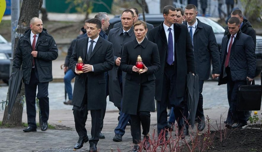 Ukrainian President Volodymyr Zelenskiy, foreground left, and his wife Olena Zelenska hold candles as they walk to a memorial in Independent Square (Maidan) in Kyiv, Ukraine, Thursday, Nov. 21, 2019. The memorial is dedicated to people who died in clashes with security forces in 2013 during protests sparked by then President Viktor Yanukovych's decision in November 2013 to freeze ties with the West and tilt toward Moscow. (Ukrainian Presidential Press Office via AP)