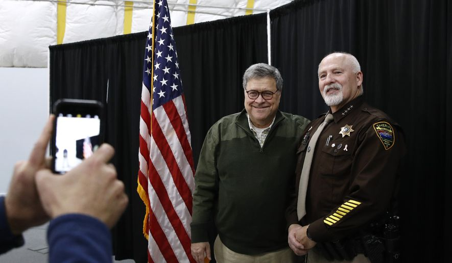 Attorney General William Barr poses for a photo with Sheriff Donald Bell of Lake County, Mont., after speaking at a law enforcement roundtable at the Flathead County Sheriff's Posse in Evergreen, Mont., Friday, Nov. 22, 2019. (AP Photo/Patrick Semansky) **FILE**