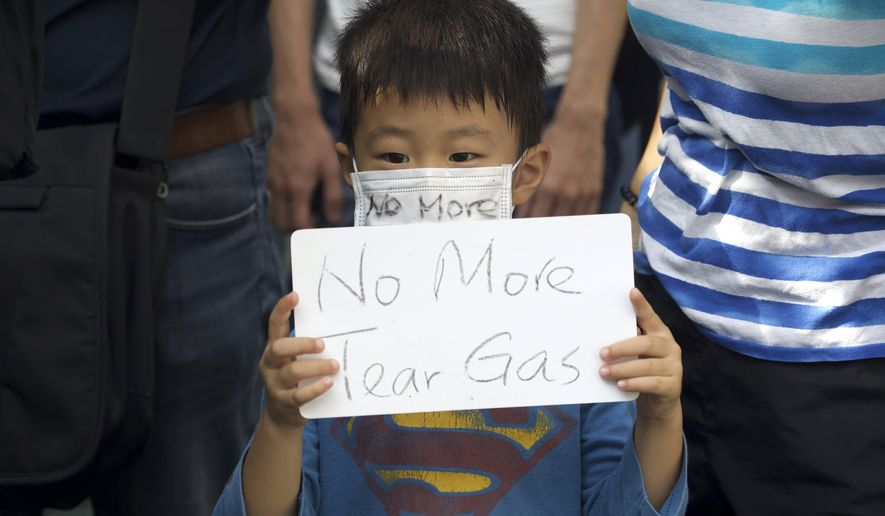 A child holds a sign during a rally to protest against the exposure of children to tear gas by police in Hong Kong, Saturday, Nov. 23, 2019. President Donald Trump on Friday wouldn't commit to signing bipartisan legislation supporting pro-democracy activists in Hong Kong as he tries to work out a trade deal with China. (AP Photo/Ng Han Guan)