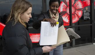 In this Wednesday, Nov. 20, 2019 photo, from left, Mary Blitzer, of the Sierra Club, gives a petition of over 23,000 signatures to Amira Adawe of the Beautywell Project as they deliver it to the Amazon Fulfillment Center in Shakopee, Minn. The two non-profit groups launched a campaign for Amazon and E-bay to stop selling toxic skin-lightening creams that contain mercury. (Christine T. Nguyen /Minnesota Public Radio via AP)