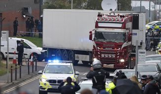 FILE - In this Wednesday Oct. 23, 2019 file photo, police escort the truck, that was found to contain a large number of dead bodies, as they move it from an industrial estate in Thurrock, south England. British police say they have arrested a 23-year-old man from Northern Ireland, Friday Nov. 22, 2019, over the deaths of 39 people from Vietnam who were found dead in a refrigerated container truck last month. (AP Photo/Alastair Grant, File)